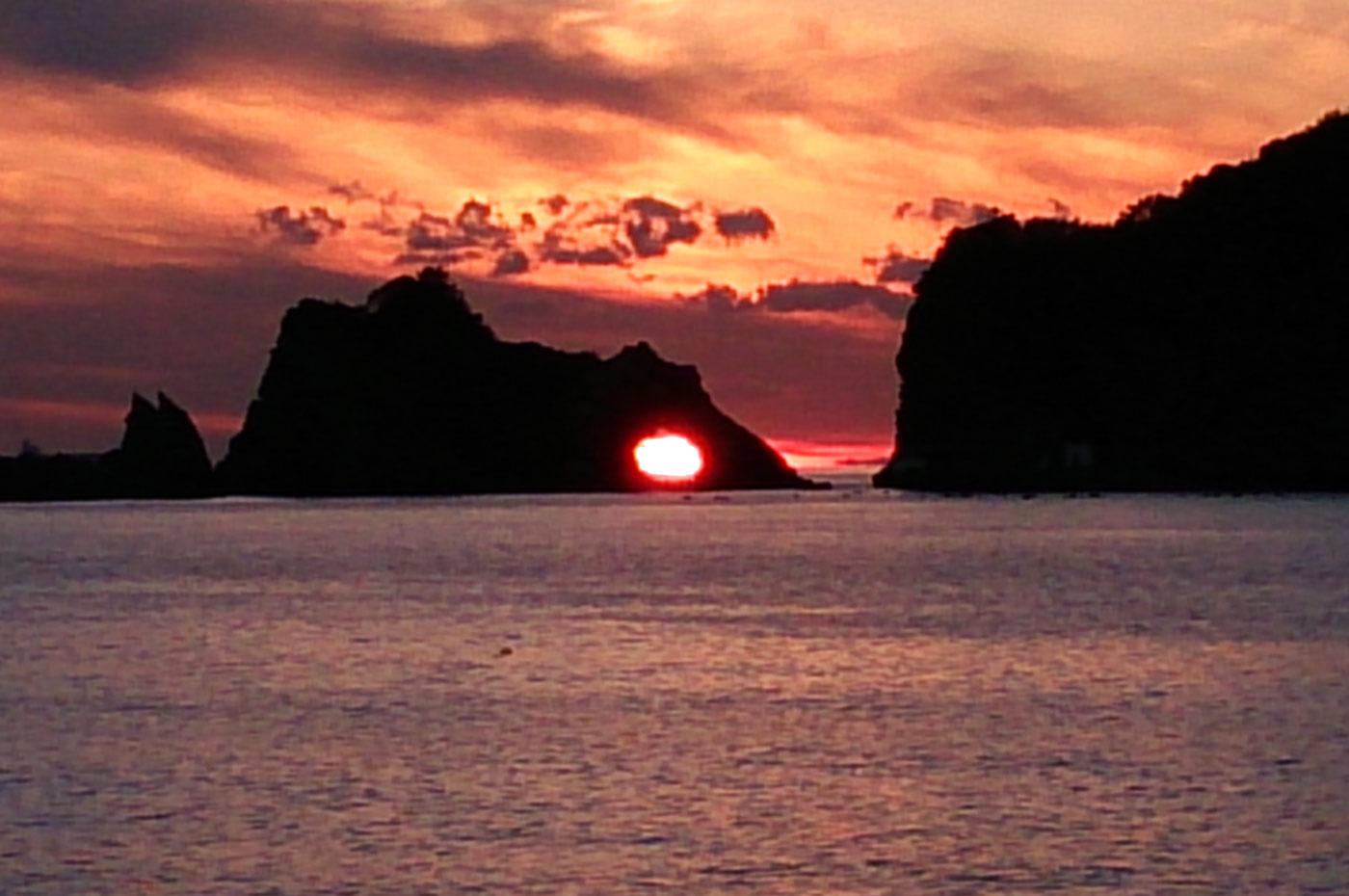 浮島の岩穴から見た夕日の画像