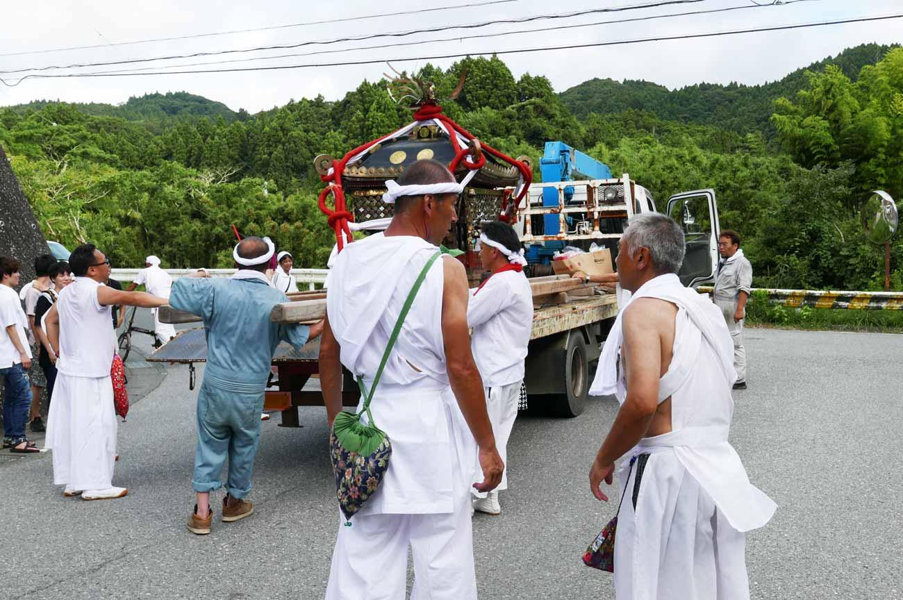 トラックで神輿を運ぶ様子