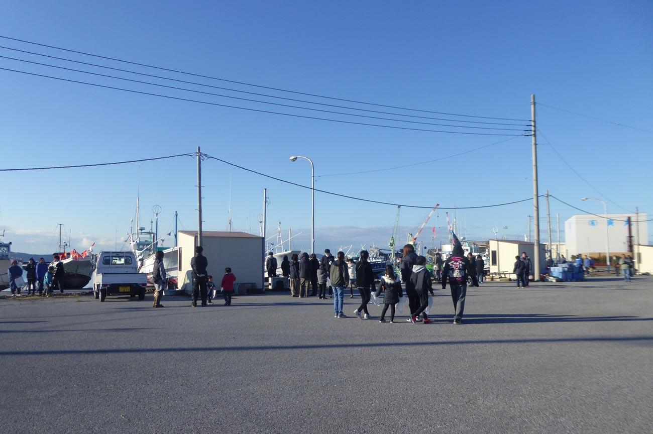 船形漁港の船揚場に集まる人々の画像